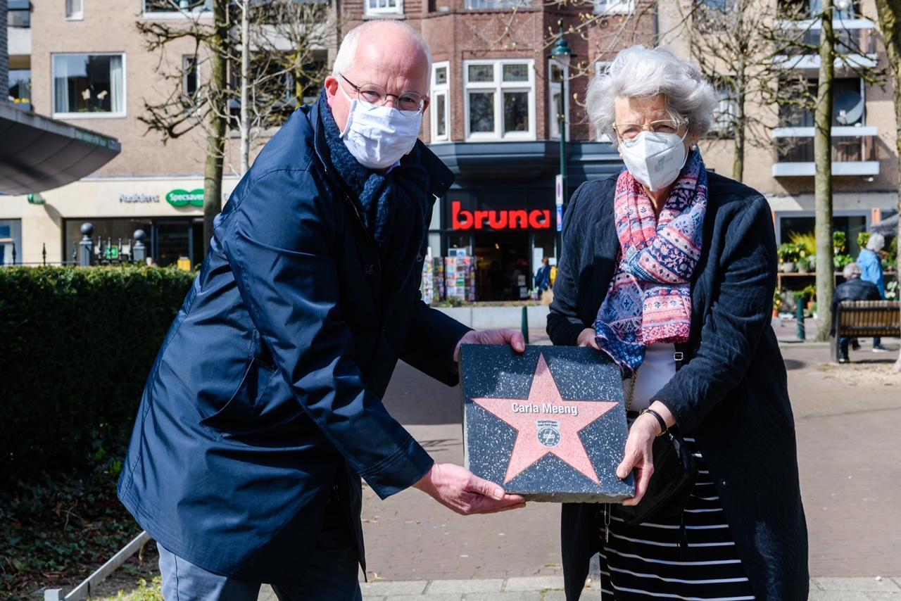 Wethouder Marcel Fluitman helpt Zeister vrijwilliger van het Jaar Carla Meeng met het plaatsen van haar Walk of Fame Steen